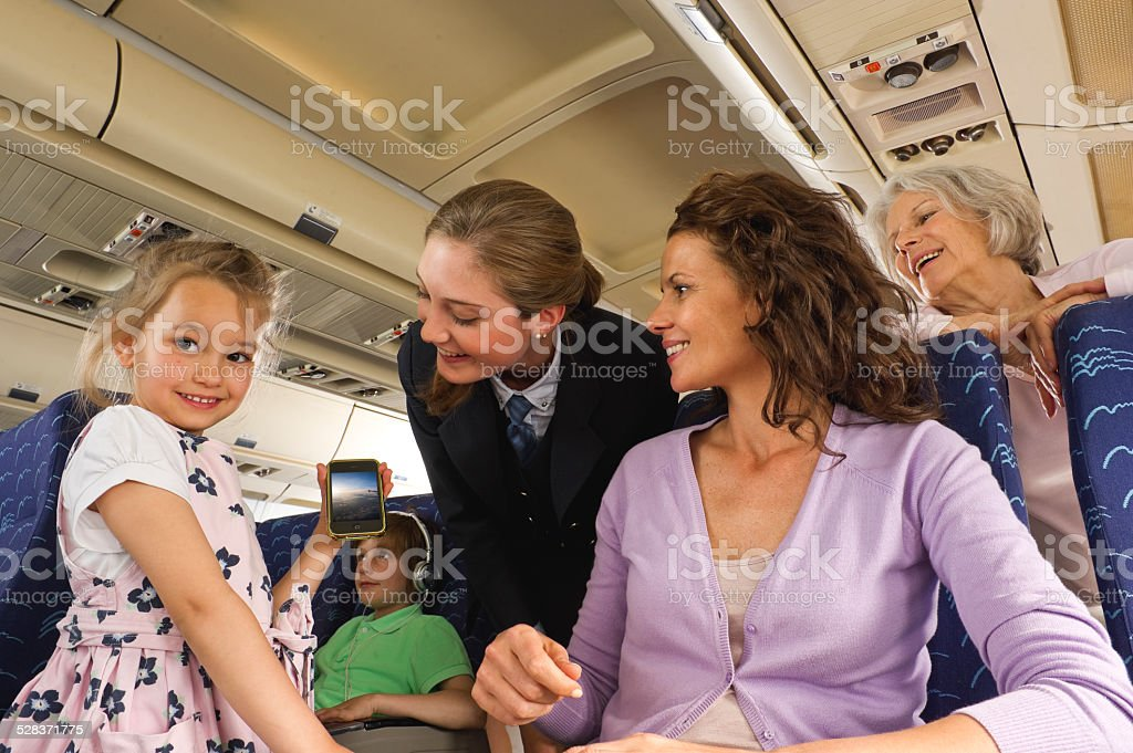 People with cell phone  on airplane People with cell phone  on airplane Adult Stock Photo