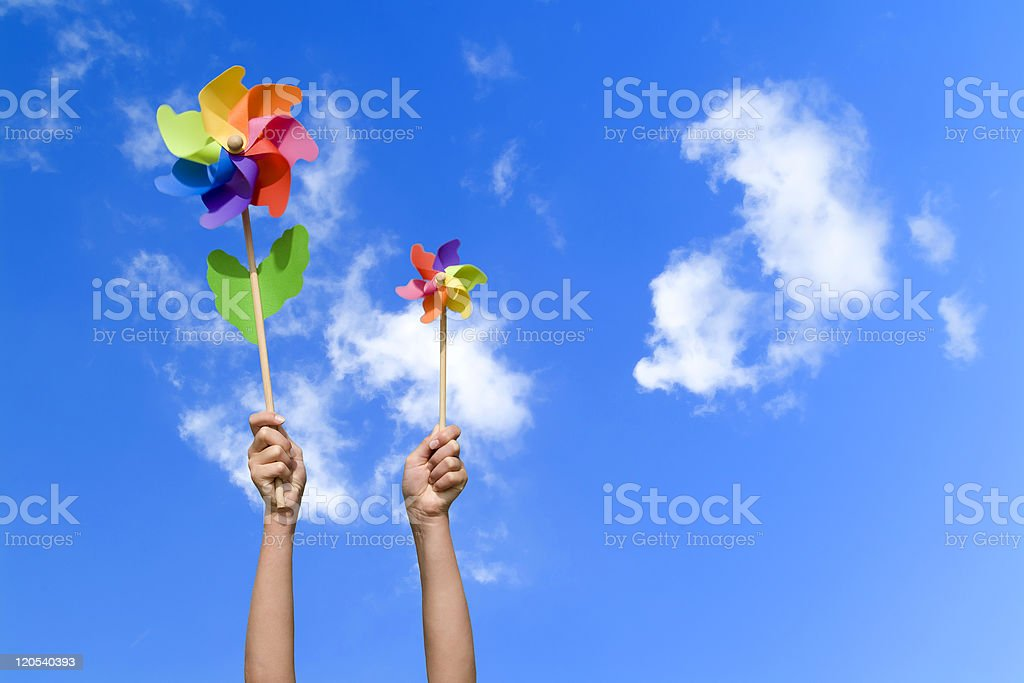 people with colorful small windmills in their hands royalty-free stock photo