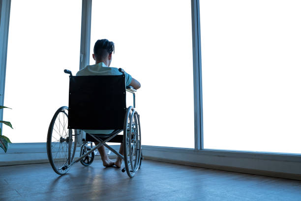 People with disabilities are sitting in a wheelchair. Looking into the window, the rear view, the image is cut for background with clipping path. stock photo