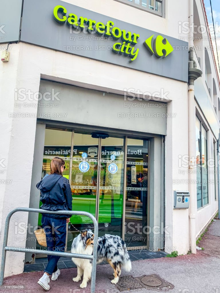 Woman with dog standing at the entrance to Carrefour city supermarket.