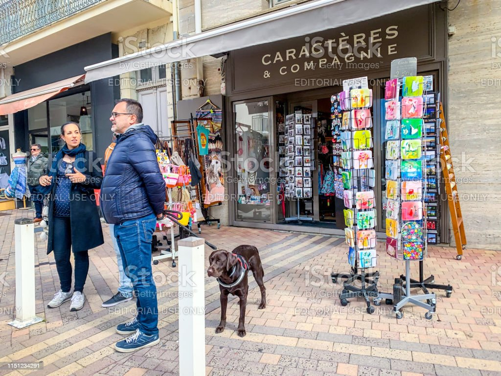 People with dog standing at the entrance to the gift shop in Biarritz...
