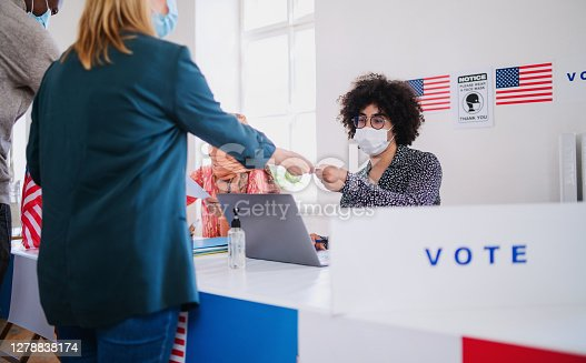 Group of people with face mask voting in polling place, usa elections and coronavirus.