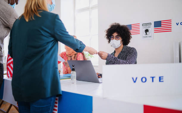 people with face mask voting in polling place, usa elections and coronavirus. - polling place stock pictures, royalty-free photos & images