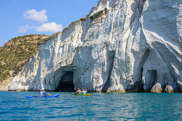 People with kayaks exploring the caves, Melos, Greece stock photo