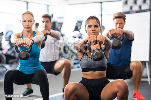 Women and men exercising with kettlebells in gym. Group of young people doing a kettle bell exercise along with squatting. Fitness class and girls training by weights.