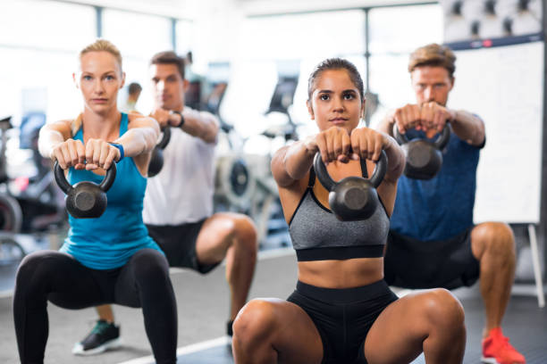 people with kettlebells squatting - class стоковые фото и изображения