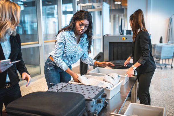 People with luggage at security check in airport stock photo