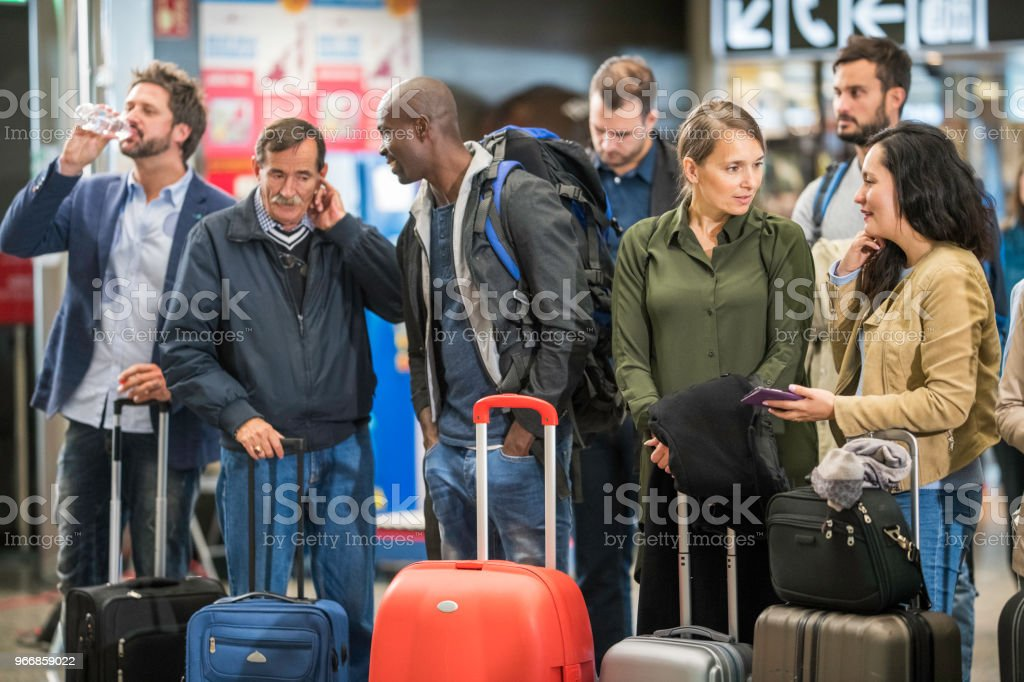 Group of people waiting and talking to each other at an airport...