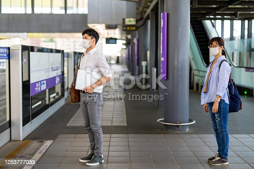 people wear surgical mask face protection and keep social distancing while waiting in line at metro or train station
