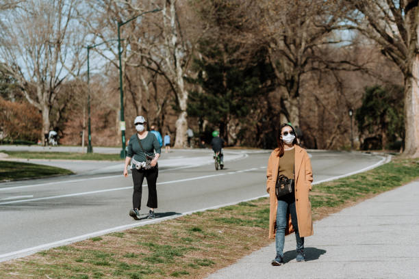 People with masks walking in Central Park stock photo