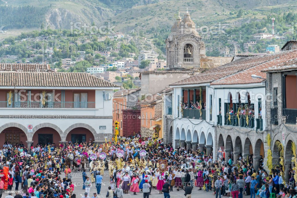 People with multicolored dresses and hats and a marching band during the celebration of the Palm Sunday of Easter at Ayacucho city, Peru. stock photo