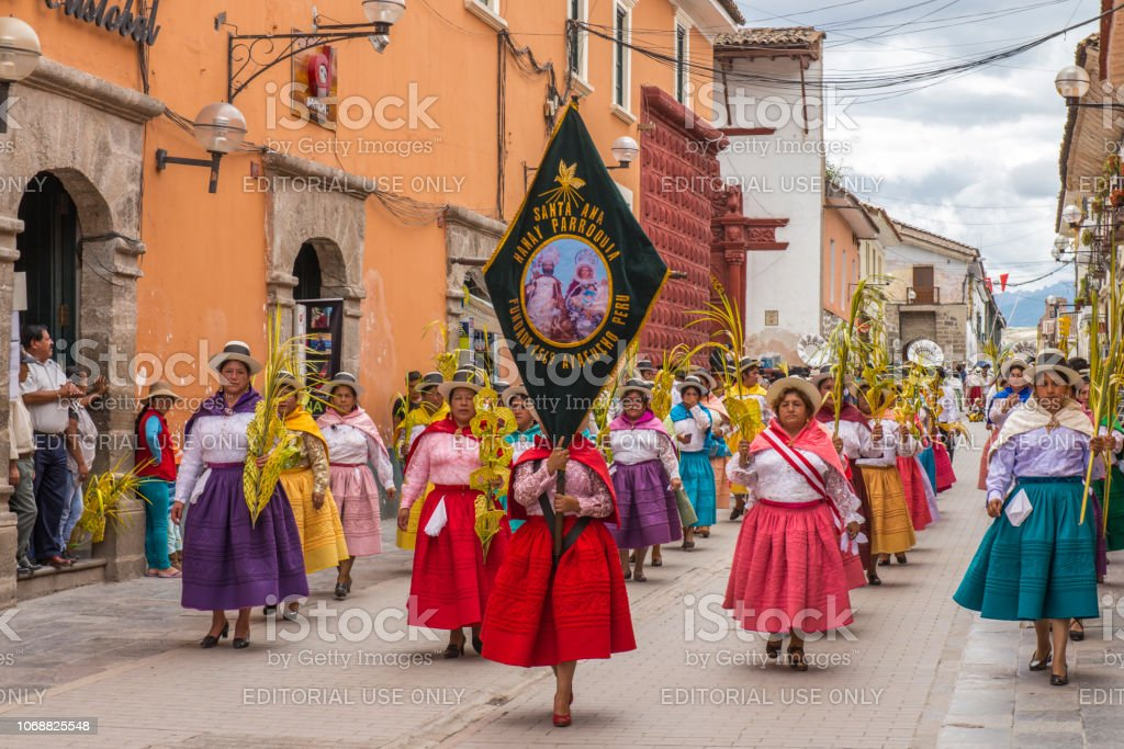 People with multicolored dresses and hats marching during the celebration of the Palm Sunday of Easter at Ayacucho city, Peru. stock photo