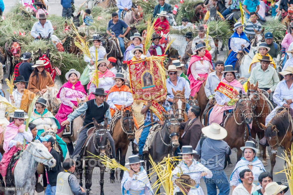 People with multicolored dresses and hats riding horses during the celebration of the Palm Sunday of Easter at Ayacucho city, Peru. stock photo