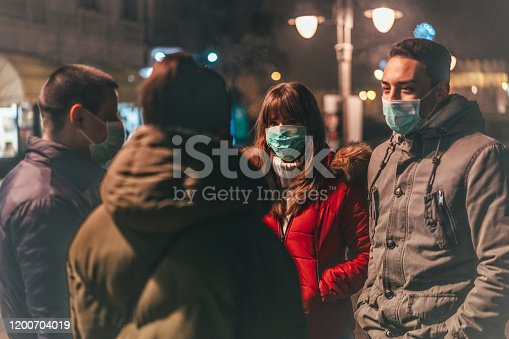 Group of young people with pollution masks talking on street.