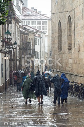 Pilgrims and tourists walking on a rainy day street of old town of Santiago de Compostela