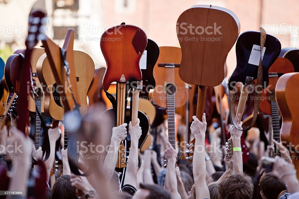 People with raised guitars Crowded place with people playing on guitars Adult Stock Photo