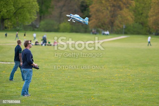Gera, Germany - April 30, 2016: People with remote controllers at model aircraft show in Gera, Germany with one of the flying objects. At the open celebration called Hofwiesenparkfest, a lot of people show their work or hobby or sell goods. In the background some visitors walking trough the park
