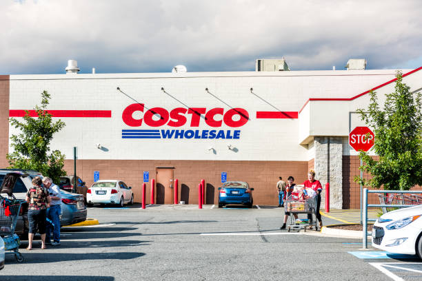 People with shopping carts filled with groceries goods, products walking out of Costco store in Virginia in parking car lot stock photo