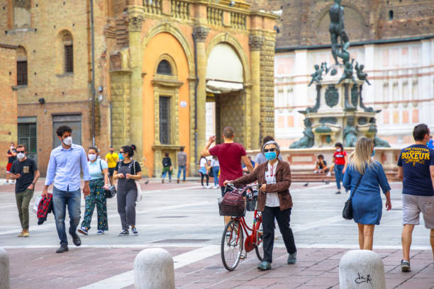 menschen mit chirurgischer maske in bologna italien - standbildaufnahme stock-fotos und bilder