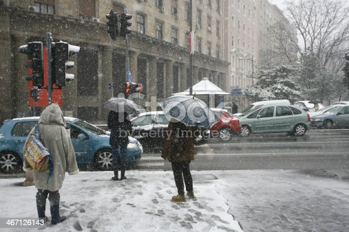 istock People with umbrella during snow storm car pedestrian 467126143