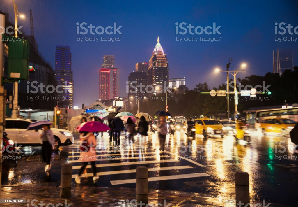 City view of Taipei with rain and people crossing the street at night