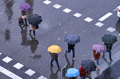 People with umbrellas in different colors crossing a street while snowing in Madrid