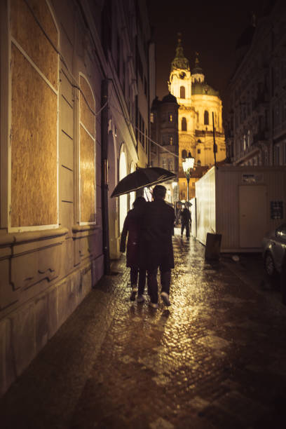 people with umbrellas silhouettes, in the rain in old Prague center stock photo