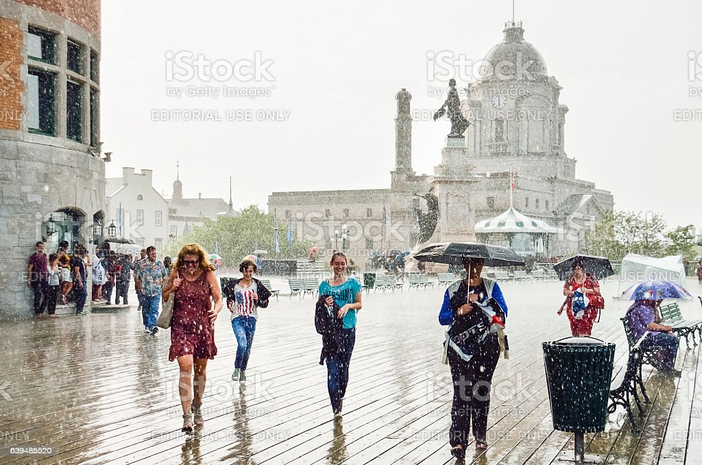 People with umbrellas walking in heavy rain on dufferin terrace stock photo