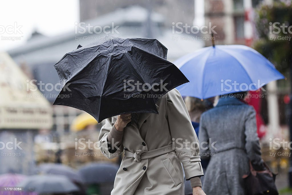 people with umbrellas walking in the city stock photo