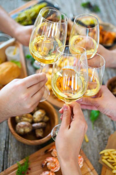 menschen mit weißen wein toasten über serviert tisch mit essen. - griechische partyspeisen stock-fotos und bilder