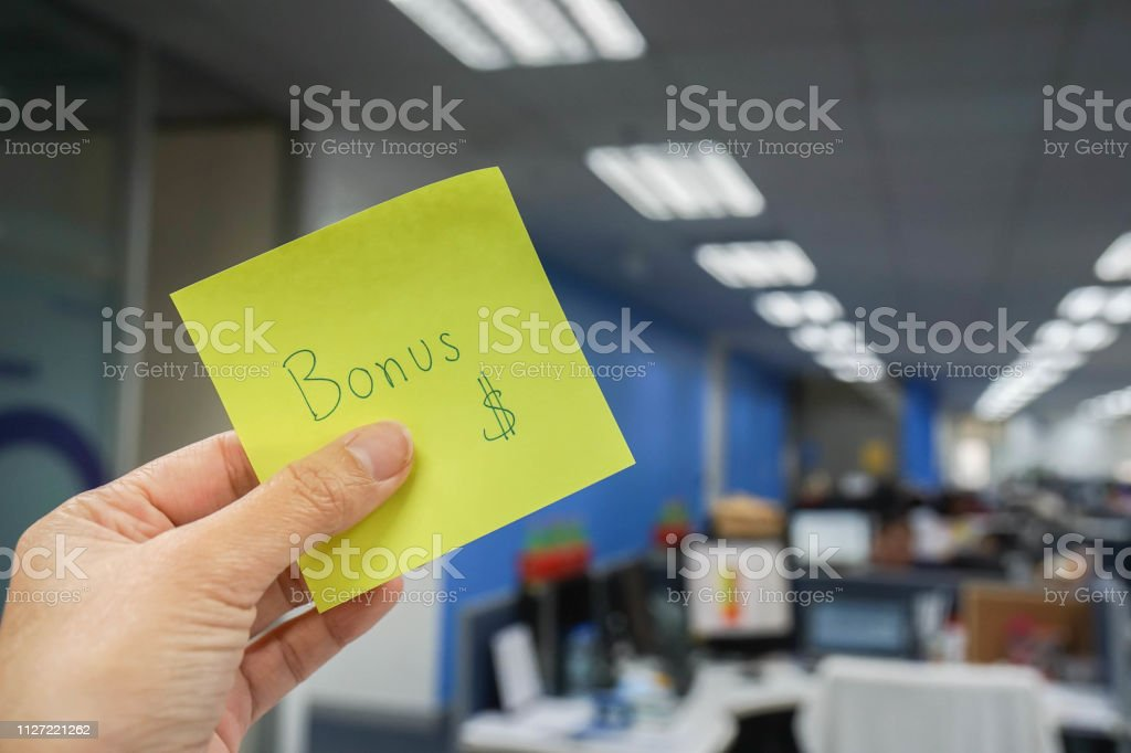 people with yearly bonus written on yellow sticky note in left hand stock photo