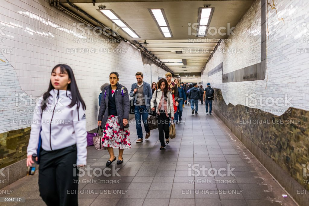 People woman walking in underground transit by sign in NYC Chelsea West Side 34th Street Hudson Yards Subway Station after work on commute stock photo