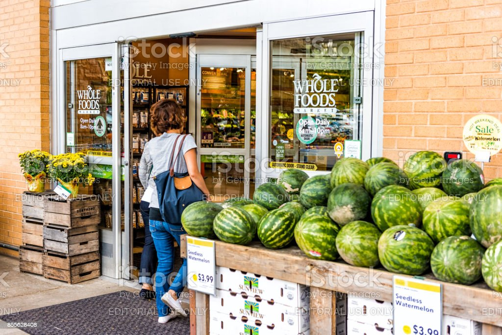 People, women, female entering Whole Foods Market grocery store building in city in Virginia with autumn displays and watermelons stock photo