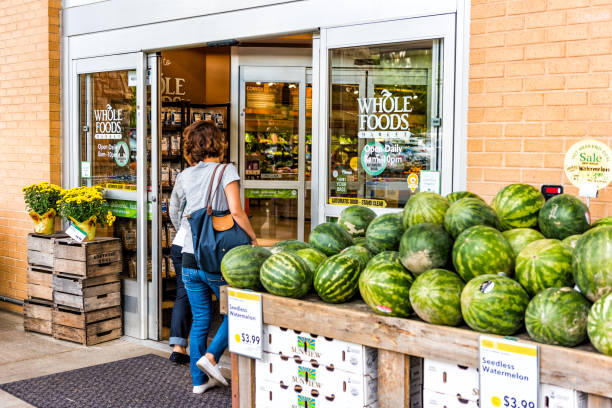 people, women, female entering whole foods market grocery store building in city in virginia with autumn displays and watermelons - food logo stock photos and pictures