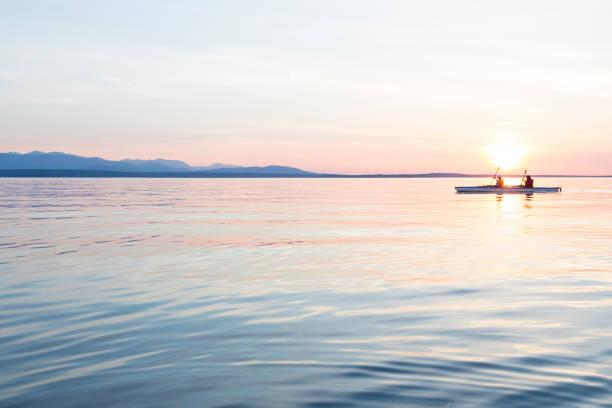 People women sea kayaking paddling boat in calm water together at sunset. Active outdoor adventure water sports. Journey, destination, teamwork concepts. People women sea kayaking paddling boat in calm water together at sunset. Active outdoor adventure water sports. Journey, destination, teamwork concepts. puget sound stock pictures, royalty-free photos & images