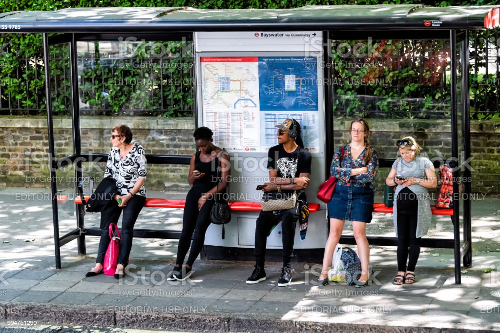 People women waiting for bus at stop tired during day standing under cover, signs for Bayswater Queensway Underground tube metro on street road in city stock photo