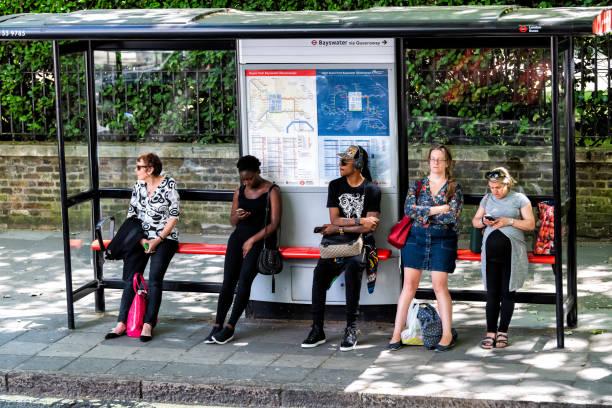 mensen vrouwen wachten op bus aan halte moe tijdens de dag staan onder dekking, buis tekenen voor bayswater queensway ondergrondse metro op straat weg in de stad - bushalte stockfoto's en -beelden