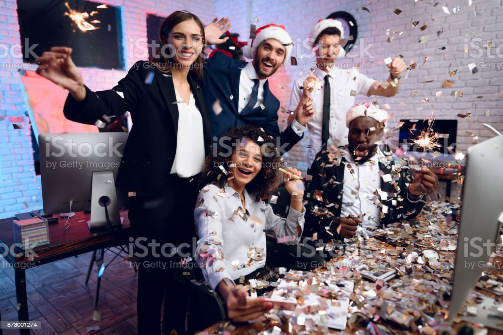 人々 は新しい年にオフィスで働きます。彼らはオフィスで新年を満たすために準備しています。周りには、紙吹雪を飛ぶ。 ストックフォト