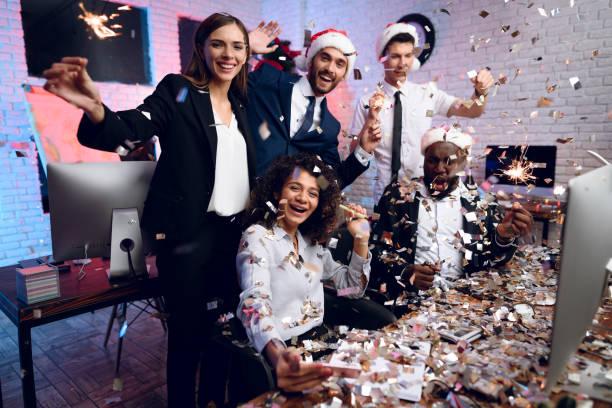 人々 は新しい年にオフィスで働きます。彼らはオフィスで新年を満たすために準備しています。周りには、紙吹雪を飛ぶ。 - 社内パーティ ストックフォトと画像