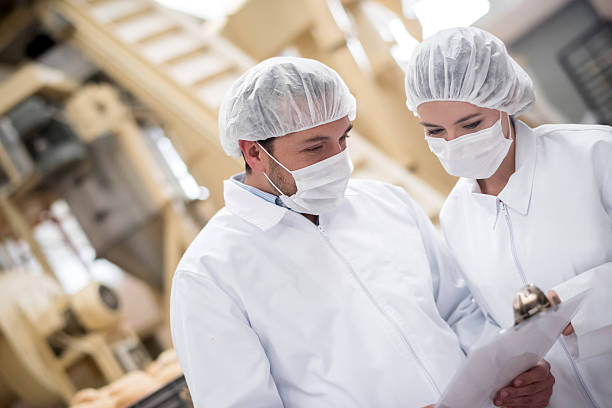 People working at a food factory People working at a food factory doing quality control and reading documents on a clipboard hair net stock pictures, royalty-free photos & images