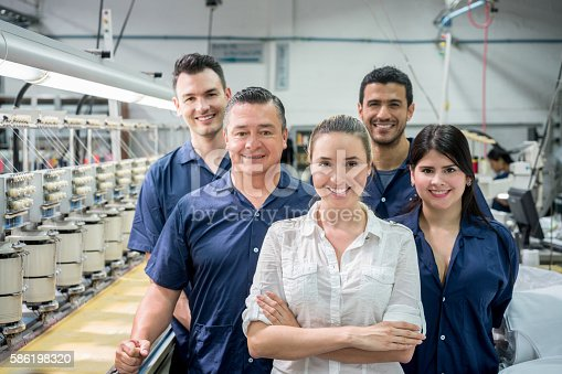 Group of people working at an embroidery factory and looking at the camera smiling