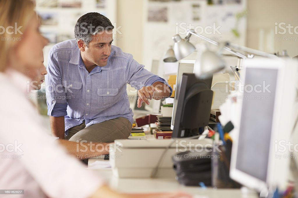 People working at desks in a busy and creative office stock photo