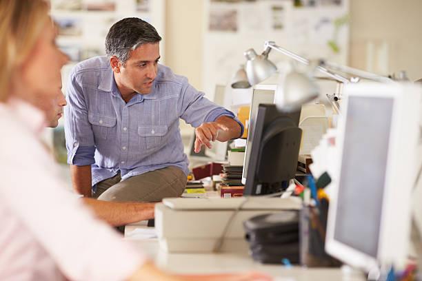travailleurs au bureau en bureau créatif occupé - graphisme photos et images de collection