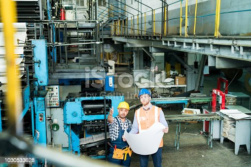 Factory worker showing the work of machines to the manager standing with blueprint
