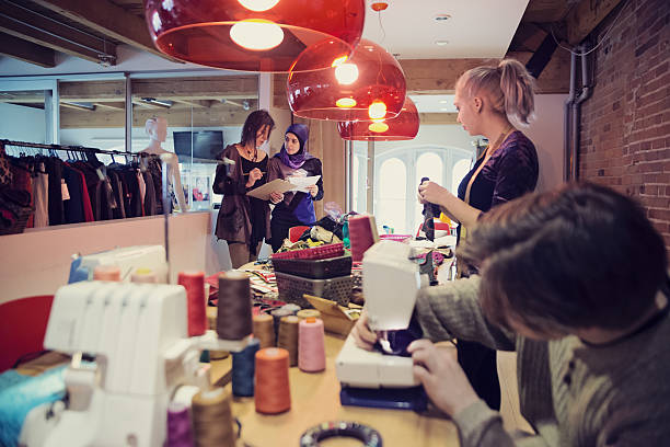 People working in small fashion enterprise lead by woman. - Photo