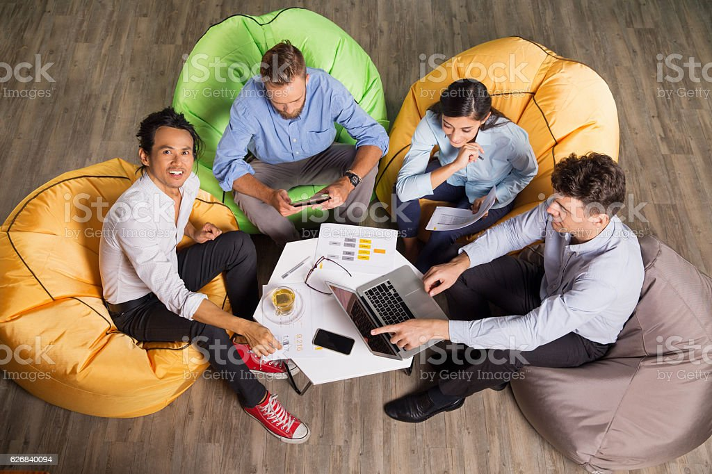People Working on Beanbag Chairs in Trendy Office stock photo