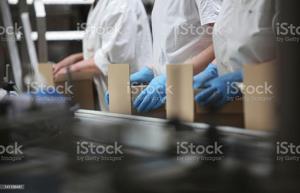 people working on packing line in factory stock photo