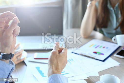 Selective focus on company workers hands. Male arms do explaining gestures and hold metallic ball pen. Female in blue trendy blouse writing something on paper folder