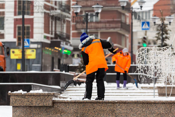 People-janitors in orange jackets cleaned the city from snow with shovels. Winter city after a snowfall People-janitors in orange jackets cleaned the city from snow with shovels. Winter city after a snowfall. street sweeper stock pictures, royalty-free photos & images