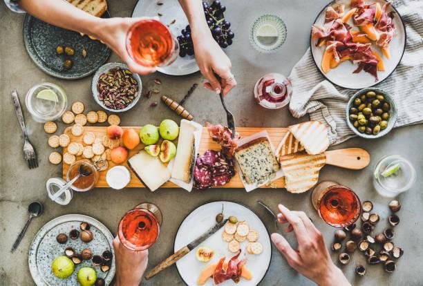 人們手拿一杯玫瑰酒在野餐桌上 - 即食口糧 個照片及圖片檔